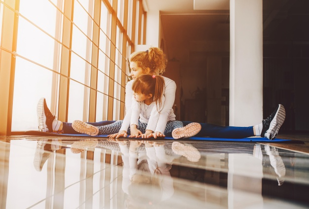 madre-e-hija-sentadas-en-el-suelo-haciendo-yoga_1153-2027