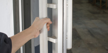 Close-up of hand open Aluminum glass door or Hand holding handle